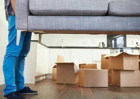 Man moving a sofa in home